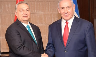 Two men in suits shake hands.