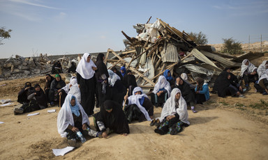 Women sit in front of ruins of demolished home.