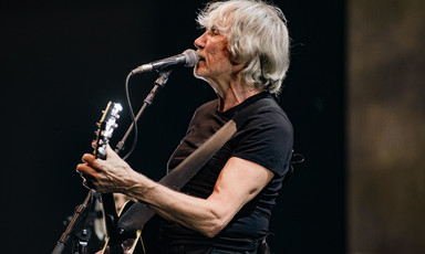 Roger Waters singing through a microphone with guitar.