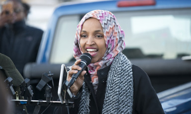 Representative Ilhan Omar speaks into a microphone.