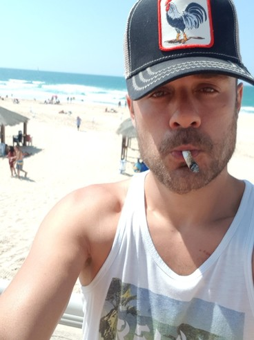A man on a beach wears a baseball cap and smokes a cigarette