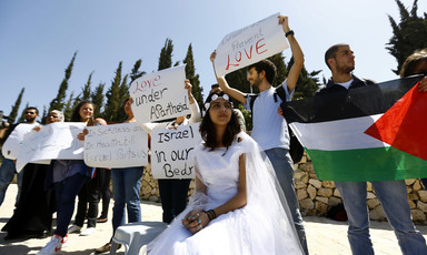 A young woman in a bridal grown sits in front of protesters holding signs