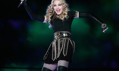 Madonna dancing on stage and holding microphone in one hand