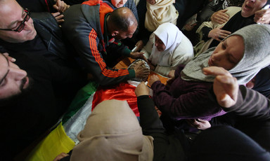 Men and women crowd around body shrouded in Palestine flag