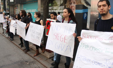 About six people stand with signs calling to end Israeli violence against Palestinians