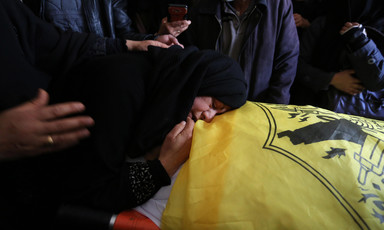 A woman mourns over body of youth wrapped in a Fatah flag.
