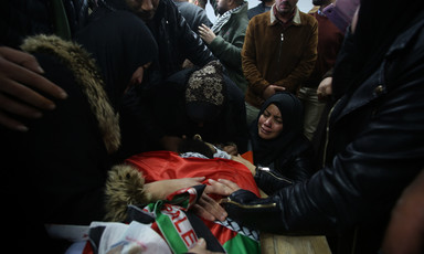 People stand and kneel around body shrouded in Palestine flag