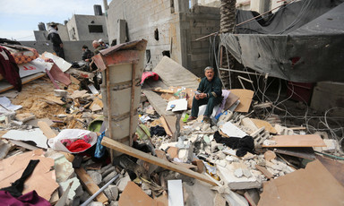 Man sits on pile of rubble and household items