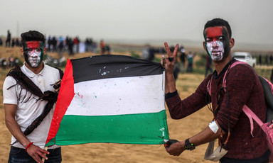Two young men with painted faces hold a Palestinian flag