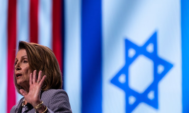 A woman at a podium in front of American and Israeli flags