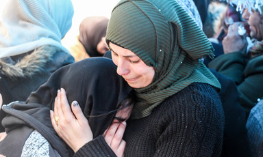 Woman cries on the shoulder of a young woman amid crowd