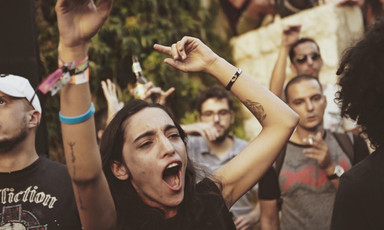A young woman dances with her hands in the air amid crowd