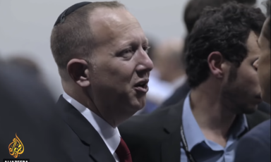 A man in a suit and red tie, wearing a kippah, a Jewish skull cap, talks to two other men.