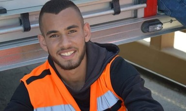 Smiling young man wearing black hoodie and high-visibility vest is seen from chest up