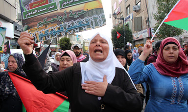 Protesters hold banners and Palestinian flags.
