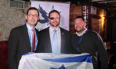 Three men holding an Israeli flag