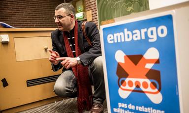 A man kneels and gestures as he speaks