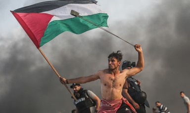 Bare-chested man wields slingshot over his head while holding Palestine flag