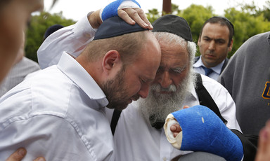 Two men, one with bandaged hands, embrace, as others look on.