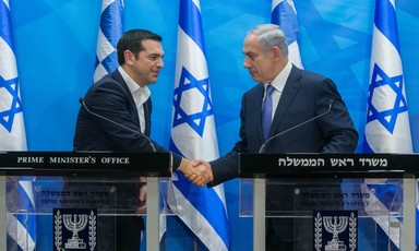 Leaders of Greece and Israel shake hands in front of Israeli flags