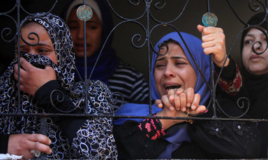 Several women crying or looking distressed stand at a window.