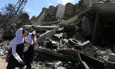 Two girls walk past rubble