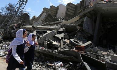 Two girls walk past rubble