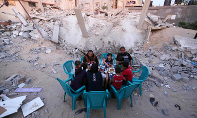 People sit around a table eating surrounded by rubble