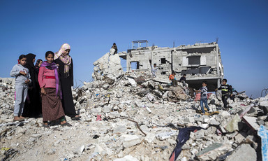 Women and children stand on the remains of a bombed-out building