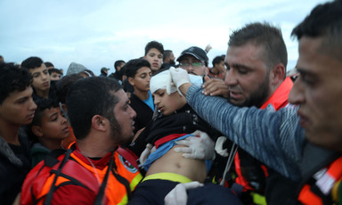 Medics hold bandage to boy's head as they carry him through crowd