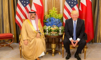 Bahrain King and Donald Trump sit side by side with American and Bahraini flags.