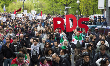 """Hundreds of people march, some with signs that say """"BDS"""""""