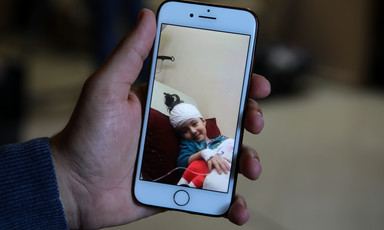 A picture on a mobile phone shows a bandaged girl smiling