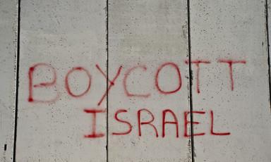 """Graffiti written in red on a grey concrete wall reads, """"Boycott Israel."""""""