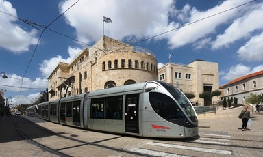 A tram passes through a street with sandstone buildings behind it