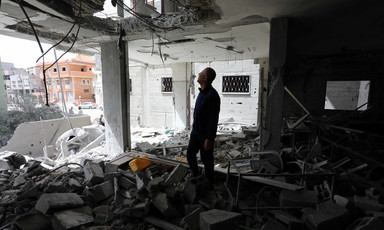 Man standing in bombed-out room looks up toward hole in ceiling