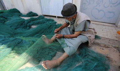 Man sits on ground with net draped over his legs