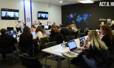A room full of people working at computers with a large Israeli flag, a world map and monitors on the walls
