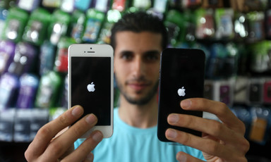 Young man holds up two iPhones in a shop