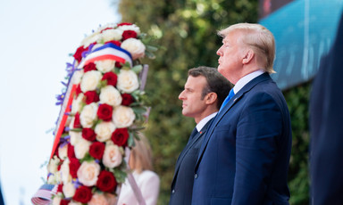 Macron and Trump stand beside a large wreath comprised of red and white roses