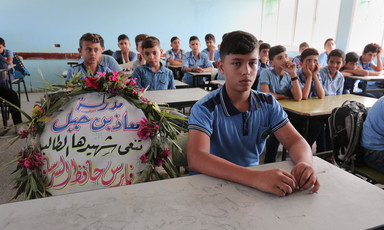 Boys sit in a classroom as a wreath with flowers and writing occupied one chair