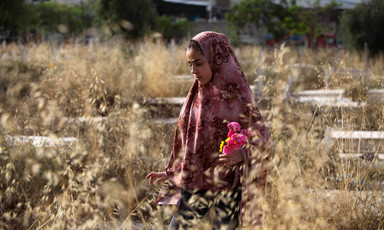 Woman wearing headscarf holds flowers in a wheat field