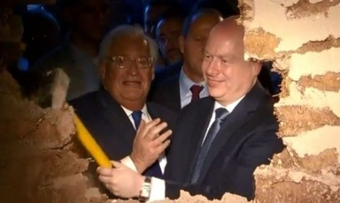 Men in suits, one holding a sledgehammer, look through hole in the wall