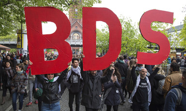 Protesters hold up big letters that spell BDS