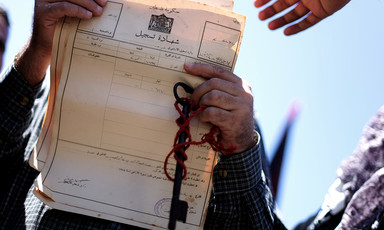 A man's hands with a key and chain wrapped around them holding up a document in Arabic