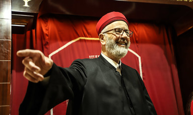 A man in religious garb gestures and smiles