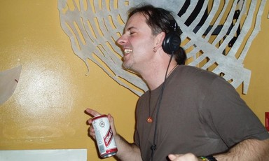 A man with headphones and a can of lager dances next to a record player