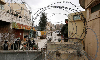 Soldiers seen behind barbed wire and walls with closed shops behind