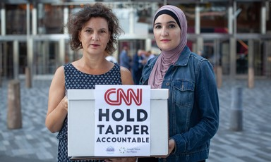 Two women hold sign