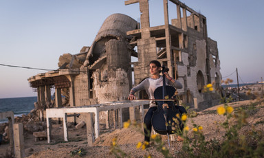 Woman plays cello in front of the rubble of a destroyed building
